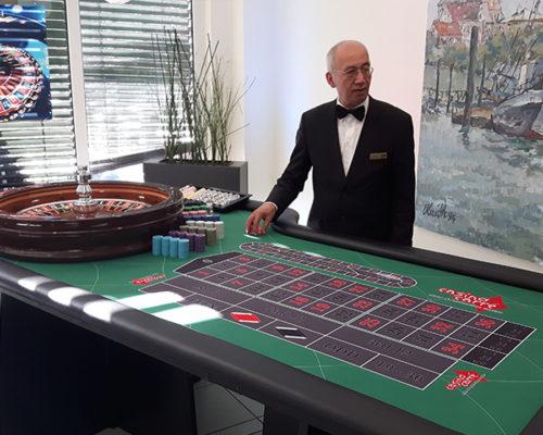 Croupier mit einem Pokertisch in einer Galerie mit Gemälden