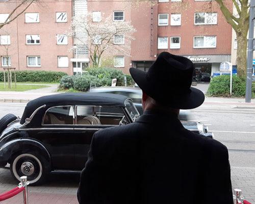 Croupier im altmodischen Kleidungsstil vor einem Käfer-Auto