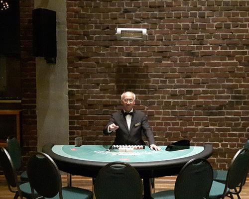 Croupier mit dem Pokertisch, vor einer hochwertigen Backsteinwand