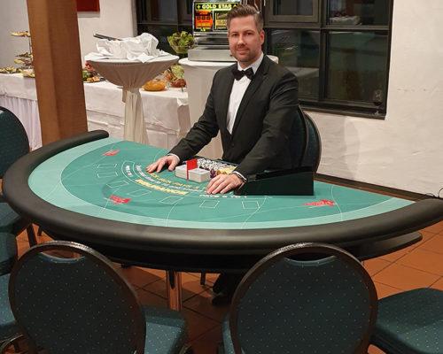 Croupier am Pokertisch im einen hell beleuchteten Raum